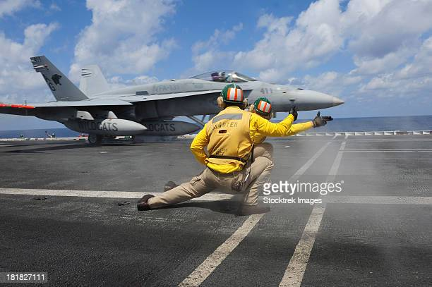 Shooters give the signal to launch an F/A-18C Hornet.