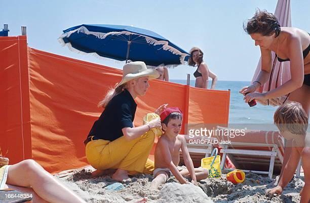 Shooting Of The Film 'La Chamade' By Alain Cavalier Plan de profil de Catherine DENEUVE coiffée d'un chapeau une cigarette à la main agenouillée...