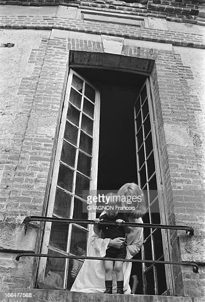Shooting Of The Film ' La Vie De Château' By JeanPaul Rappeneau Attitude souriante de Catherine DENEUVE en chemise de nuit tenant son fils Christian...