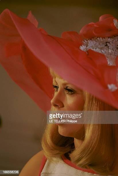 Shooting Of The Film 'Les Demoiselles De Rochefort ' By Jacques Demy Plan de troisquarts de Catherine DENEUVE chantant coiffée d'une capeline rouge...