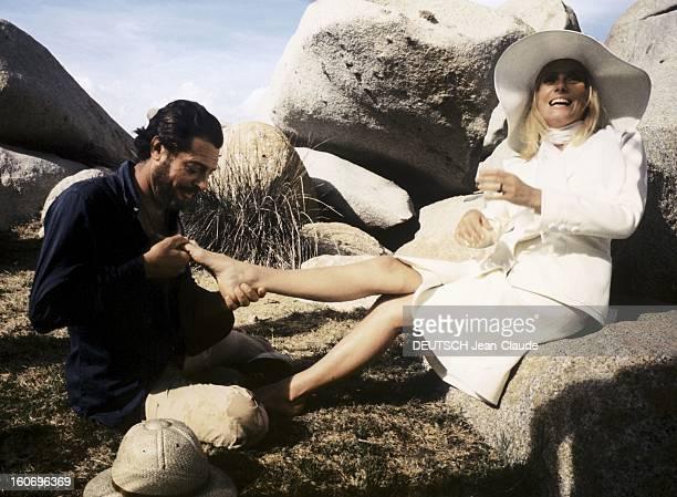 Shooting Of The Film 'Liza' By Marco Ferreri. Marcello MASTROIANNI barbu, massant le pied de Catherine DENEUVE hilare, en ensemble blanc avec chapeau...