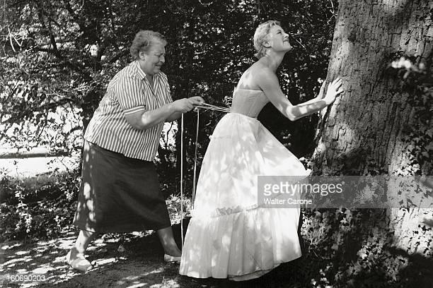 Shooting Of The Film 'marie Antoinette' By Jean Delannoy Michèle MORGAN de profil mains posées sur un arbre grimaçant tandis que son habilleuse lui...