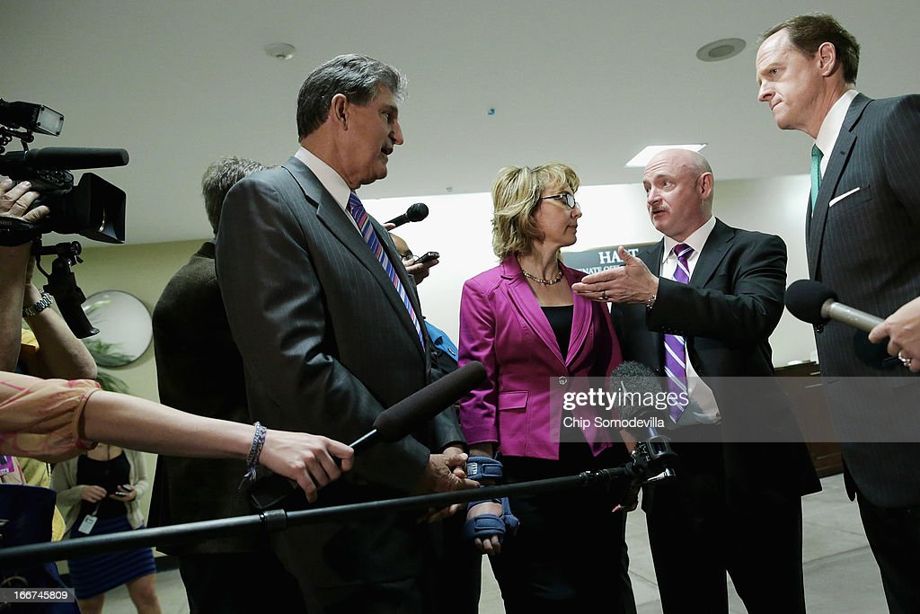 Shooting victim and former Rep. Gabrielle Giffords (D-AZ) (2nd L) and her husband and retired astronaut Mark Kelly (3rd L) join Sen. Joe Manchin (D-WV) (L) and Sen. Pat Toomey (R-PA) in the Hart Senate Office Building on Capitol Hill April 16, 2013 in Washington, DC. Giffords and Kelly met with members of Congress, including Manchin and Toomey, who have sponsored legislation to expand the background check system for gun sales.