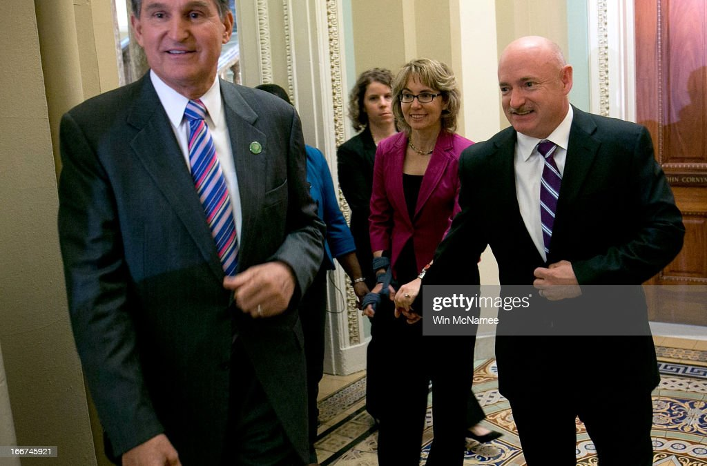 Shooting victim and former U.S. Rep. Gabby Giffords (C) is escorted by U.S. Sen. Joe Manchin (D-WV) (L) and her husband, former NASA astronaut Mark Kelly (R), while walking to a policy luncheon for Senate Democrats April 16, 2013 at the U.S. Capitol in Washington, DC. Giffords met earlier with Sen. Manchin and Sen. Pat Toomey (R-PA) on pending gun control legislation before the U.S. Senate.