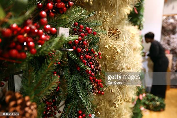A shop assistant adjusts Christmas wreaths in a John Lewis department store on December 19 2014 in London United Kingdom With just a few shopping...