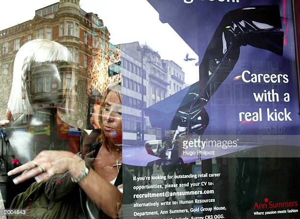 A shop assistant adjusts the bra of a model in a Ann Summers retail shop May 16 2003 in central London England The retailer which sells lingerie and...