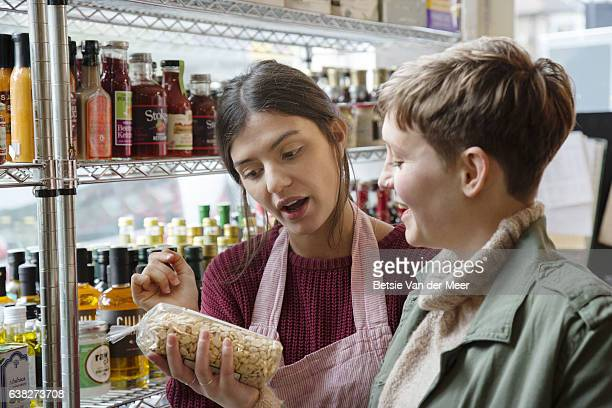 Shop assistant advices shopper on product in organic delicatessen food shop.