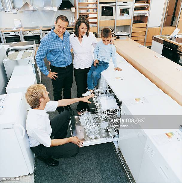 Shop Assistant Advising a Family of Three About a Dishwasher in a Department Store