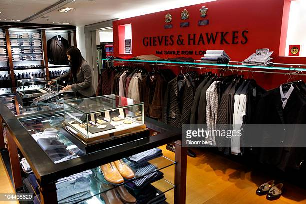A shop assistant arranges a display cabinet in a branch of Gieves Hawkes plc in Hong Kong China on Monday Sept 27 2010 Gieves Hawkes plc is an...