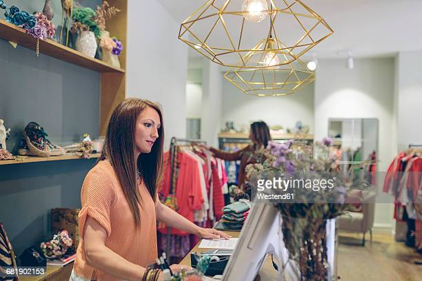 Shop assistant at counter in a boutique