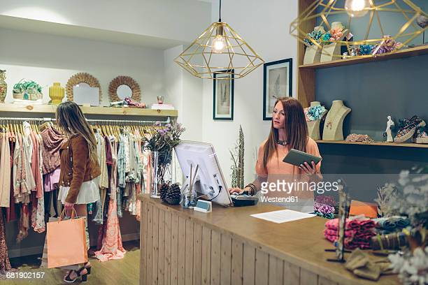 Shop assistant at counter in a boutique with customer shopping for clothes