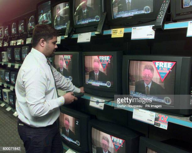 A shop assistant at the Tempo Electrical Shop in London tunes into US President Bill Clinton's grand jury testimony shown on TV worldwide today...