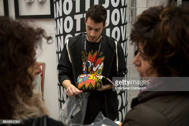 A shop assistant bags a limited edition tshirt at the 'Jova Pop Store' on December 1 2017 in Milan Italy Italian singer and songwriter Jovanotti...