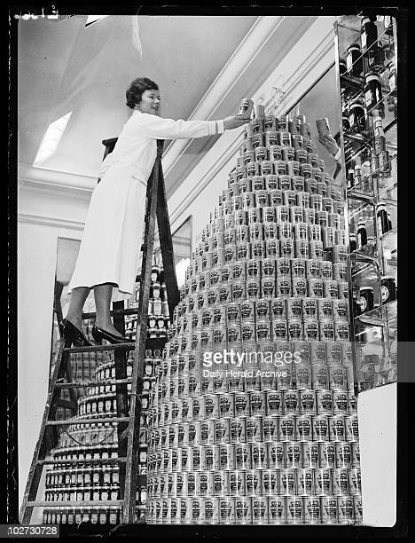 Shop assistant building giant tower of Heinz beans c 1960s A woman climbs a ladder to assemble a giant display of Heinz baked beans with pork
