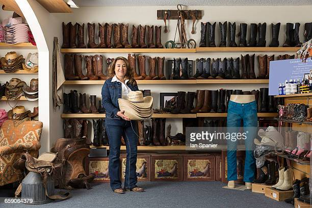 Shop assistant carrying stetsons in front of shelves of boots