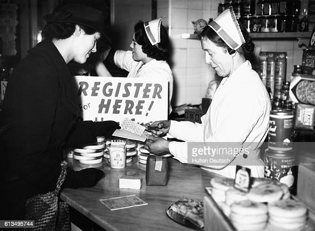 A shop assistant cuts the appropriate number of stamps from a customer's ration book as she buys groceries on the first day of rationing in London...