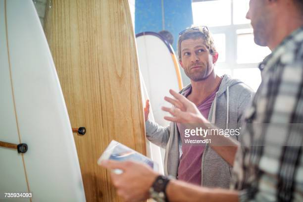 Shop assistant explaining about surfboards