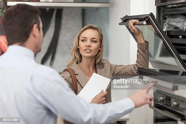 shop assistant explaining oven to customer - aparelho de linha branca - fotografias e filmes do acervo