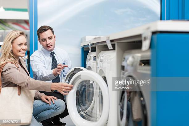 Shop assistant explaining washing machine to customer