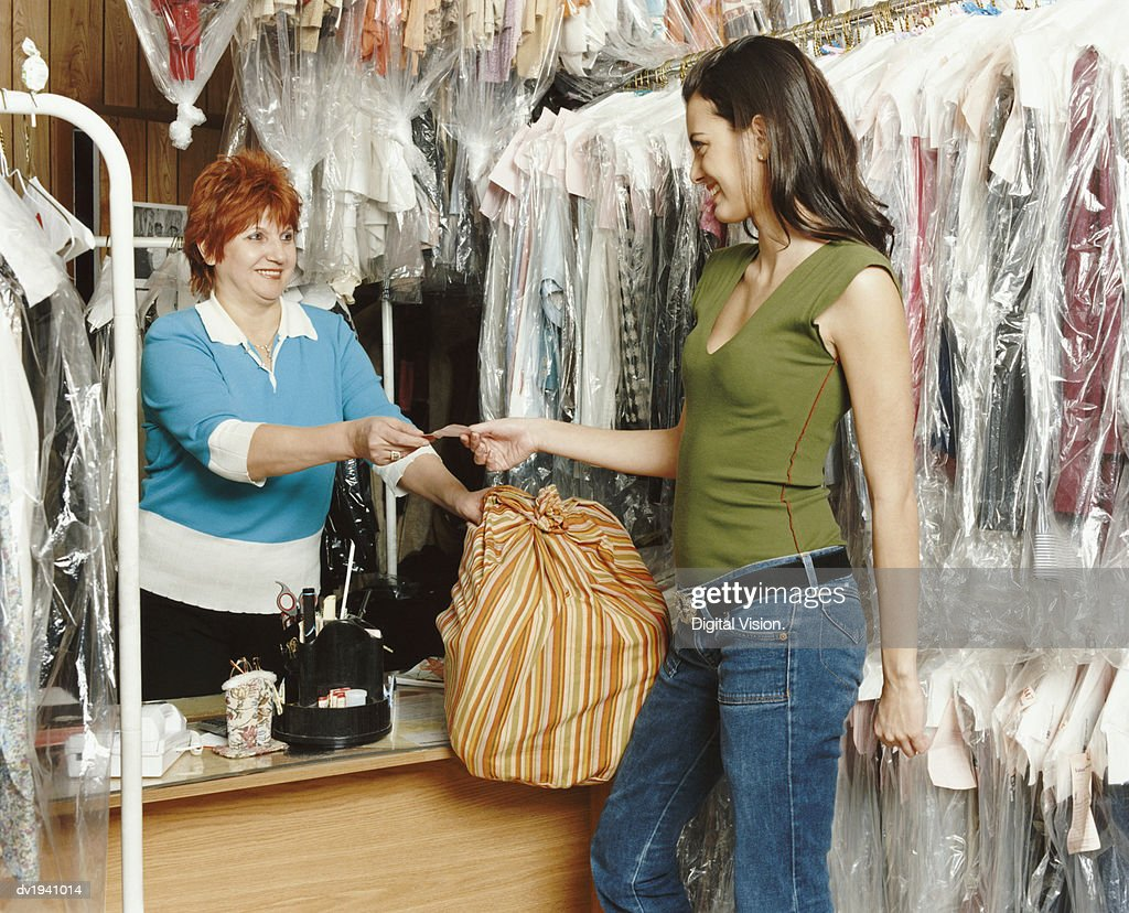 Shop Assistant Giving a Ticket to a Customer in a Dry Cleaners : Stock Photo