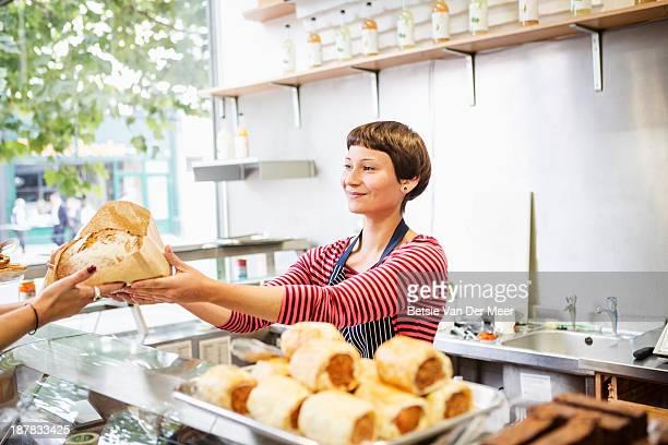 Shop assistant handing bread to customer.