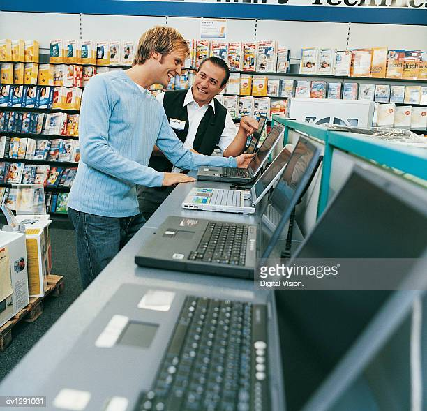 Shop Assistant Helping a Customer With a Laptop in a Computer Shop