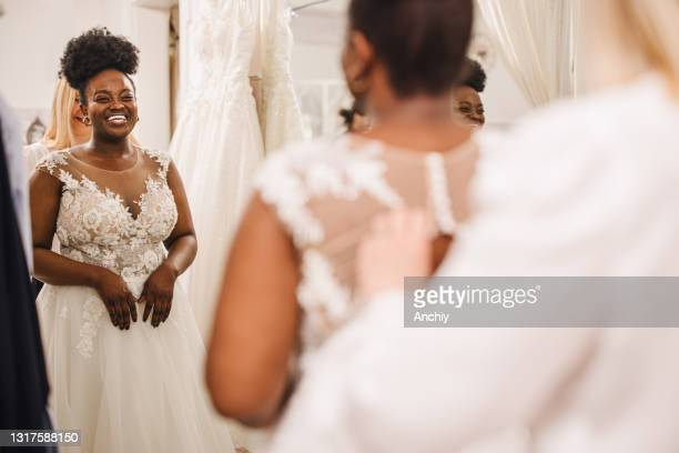 shop assistant helping bride get into wedding dress - wedding dress stock pictures, royalty-free photos & images