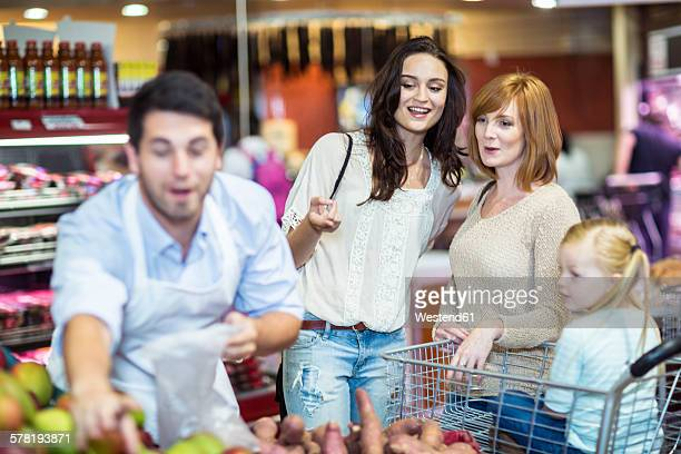 Shop assistant helping customers choosing fruits