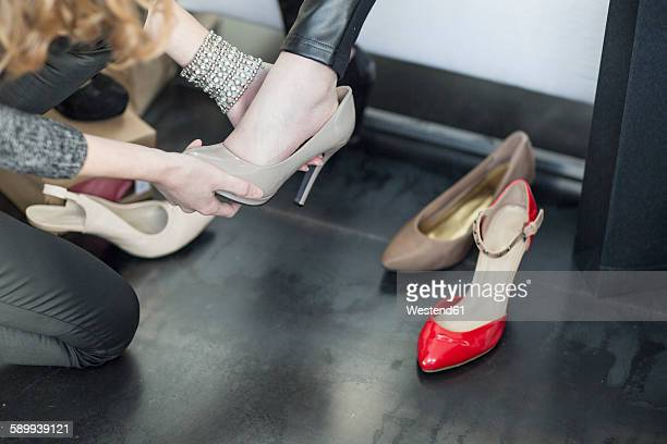 Shop assistant helping woman trying on new shoes