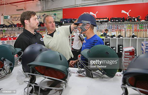 A shop assistant helps a father and son choose a cricket helmet at the Greg Chappell Cricket Centre store on November 28 2014 in Melbourne Australia...