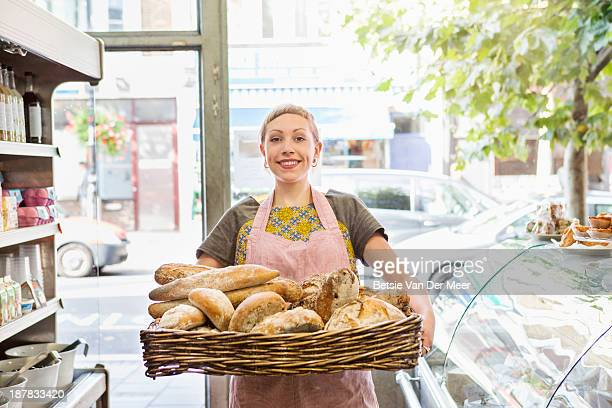 Shop assistant holding basket with artisanbreads