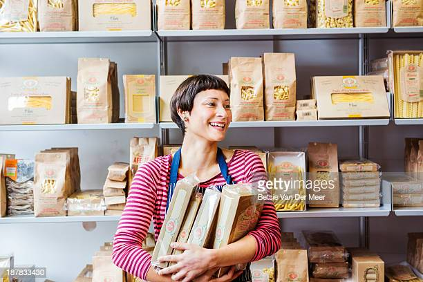 Shop assistant holding boxes in front of shelves.