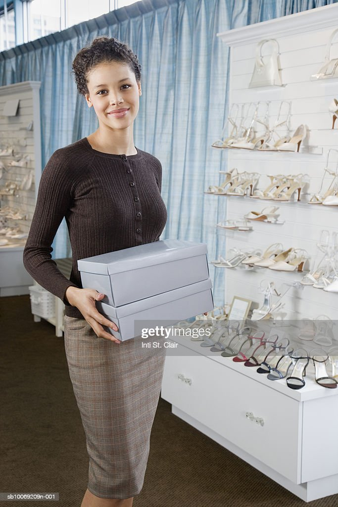 Shop assistant holding shoe boxes in wedding shop, portrait : Stockfoto