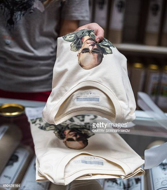 A shop assistant holds one of the Tshirts with images of Russia's President Vladimir Putin being displayed for sale at GUM one of the oldest...