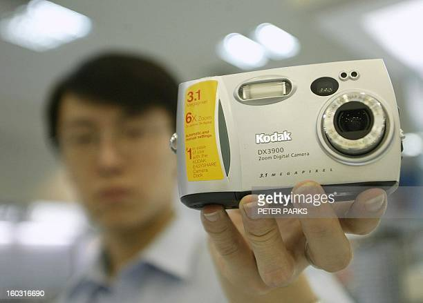 A shop assistant holds up a Kodak digital camera in a Beijing department store 27 May 2003 Film giant Kodak plans to increase the value of loans...