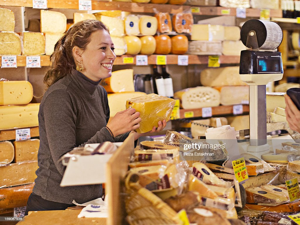 Shop assistant in cheese shop smiles at customer : Stock Photo