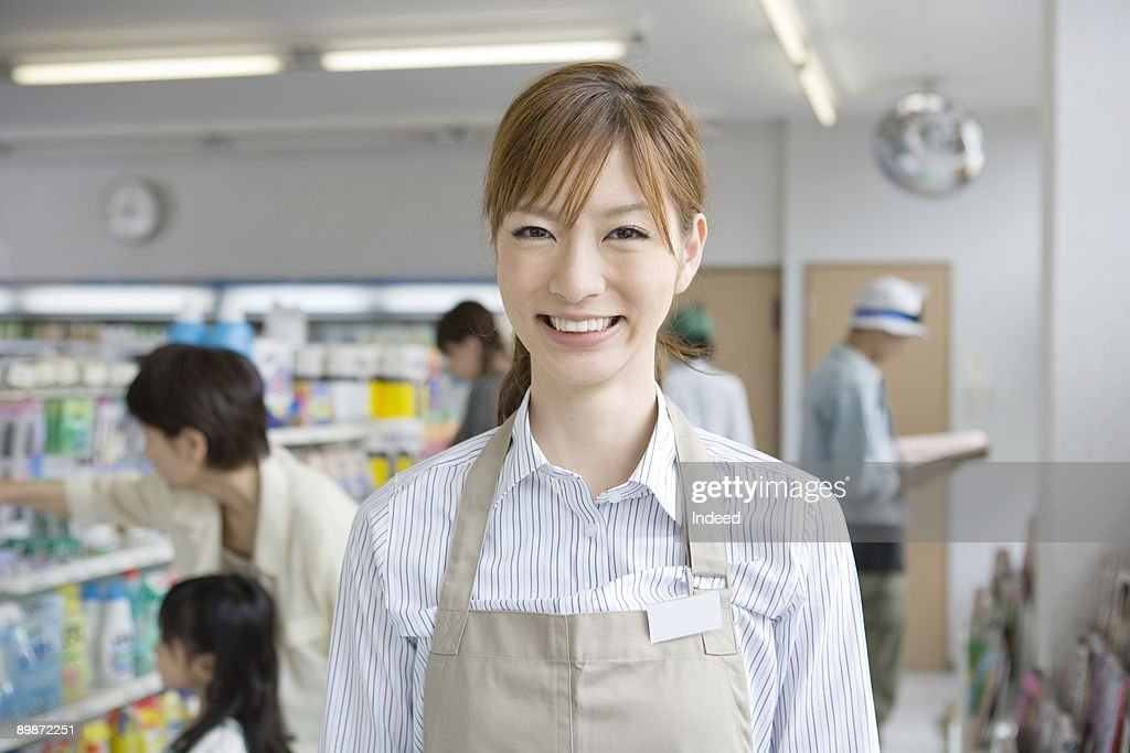 Shop assistant in convinience store, smiling : Stock Photo