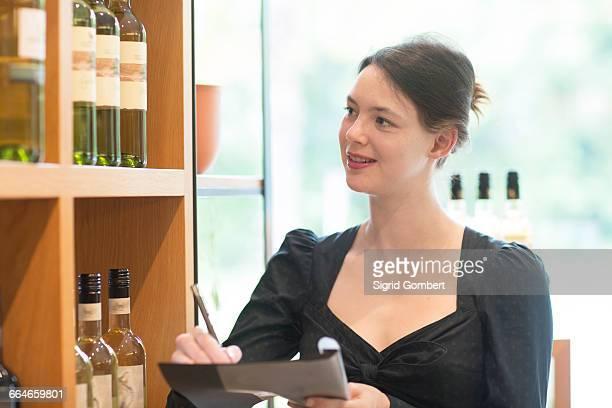 shop assistant in wine shop doing stock taking - sigrid gombert stockfoto's en -beelden