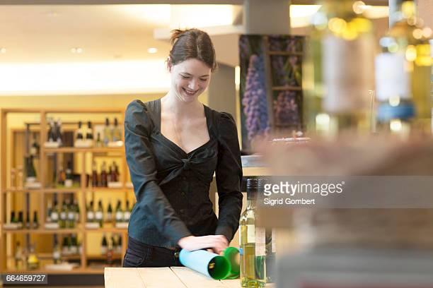 shop assistant in wine shop wrapping bottle of wine in tissue paper - sigrid gombert stockfoto's en -beelden
