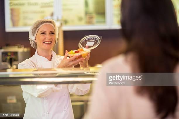 Shop assistant packing fruit salad for customer