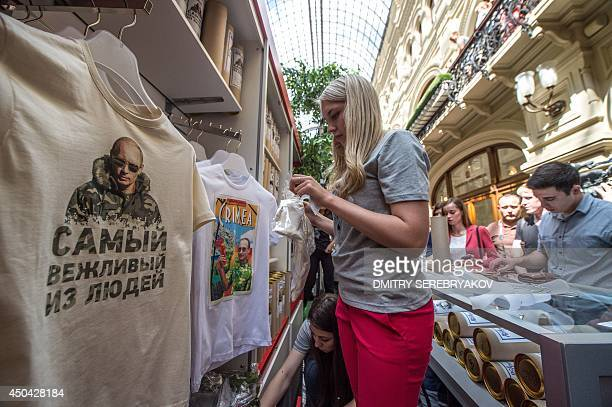 A shop assistant packs one of the Tshirts with images of Russia's President Vladimir Putin being displayed for sale at GUM one of the oldest...