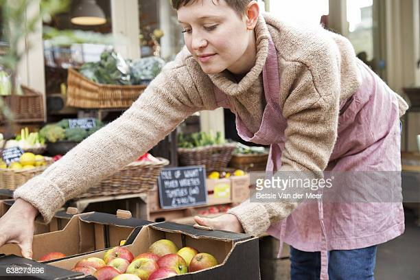 Shop assistant places crate with apples on food stall outside grocery shop.