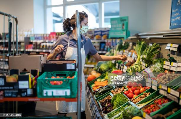 shop assistant re-stocking fresh vegetables into boxes - employee stock pictures, royalty-free photos & images