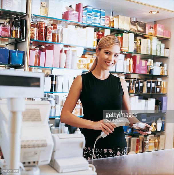 Shop Assistant Scanning Perfume at Cash Register