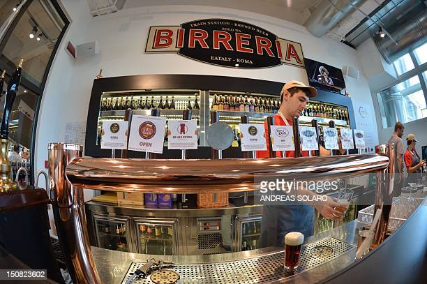 A shop assistant serves beer in the shopping area of the small craft brewery of Eataly a temple to Italian gastronomy on August 22 2012 in Rome Craft...