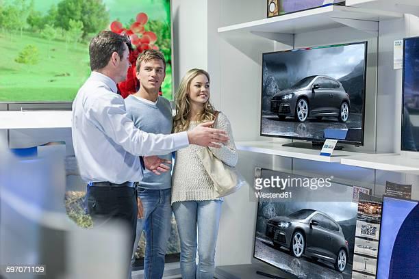 shop assistant showing flatscreen tvs to young couple - electronics store stockfoto's en -beelden