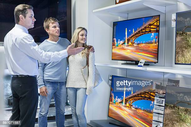 Shop assistant showing flatscreen TVs to young couple