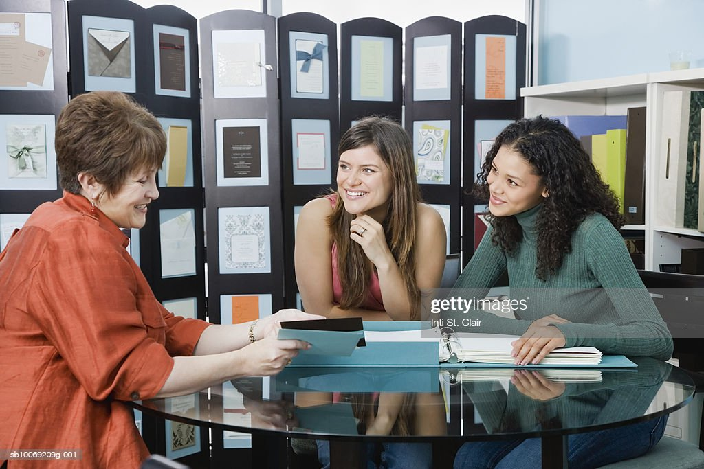 Shop assistant showing invitation sample to two young women : Stockfoto