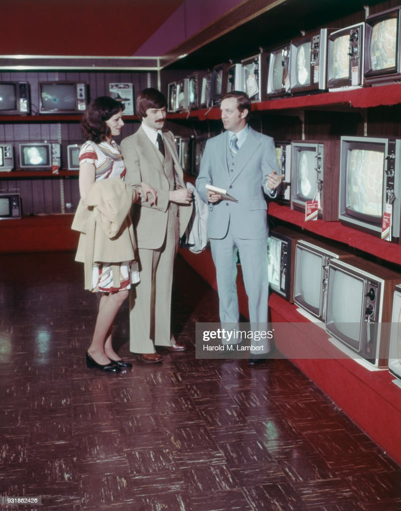 Shop assistant showing TVs to couple : News Photo