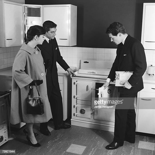 A shop assistant shows a couple of prospective buyers a Rayburn aga in a kitchen showroom circa 1960 A photoshoot for Rayburn